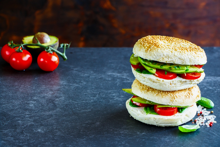 Heap of tasty bagels with avocado, cream-cheese, tomatoes and basil, rustic wooden wall background, selective focus. Clean eating, vegan, vegetarian, weight loss, healthy food concept