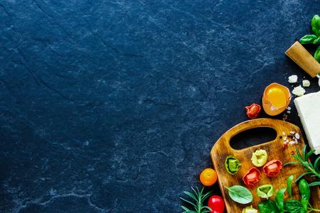 Ingredientes para cozinhar o jantar italiano. Tortellini caseiro fresco da massa, manjericão, Parmesão, alecrins e especiarias. Fundo de ardósia com espaço para texto. Vista do topo Foto de archivo - 79702807