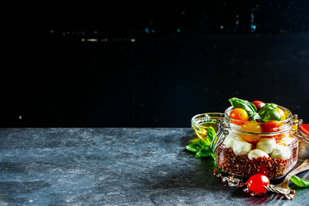 Delicious jar caprese salad with quinoa, ripe cherry tomatoes, mini mozzarella cheese and fresh basil. Detox, dieting, vegetarian, clean eating food concept. Dark rustic background, selective focus, copy space Stock Photo