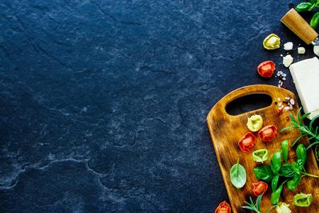 Fundo italiano do alimento com tortellini caseiro da massa, manjericão, Parmesão, alecrins e especiarias. Fundo de ardósia com espaço para texto. Vista do topo Foto de archivo - 79765828