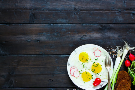 Rural breakfast set. Plate with fried eggs, radishes, green onion, sweet pepper, bread slices. Old wooden background. Top view with space.