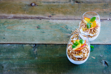 Detox breakfast set. Greek yogurt, granola, peach layered parfait in glasses with mint leaves over wooden background, copy space, selective focus. Clean eating, detox, dieting food concept