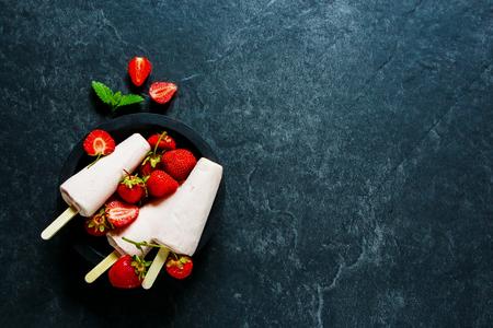 石のテーブル、新鮮なフルーツ ジュース、ビンテージ スタイル、トップ ビューで木製のボウルで有機イチゴ ヨーグルト アイス クリーム コピー ス