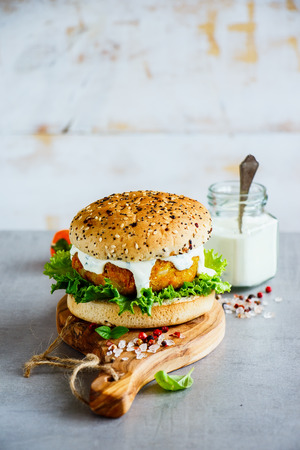 Freshly made vegan carrot and oats burger, wholegrain buns on wooden board over stone background, selective focus, copy space.