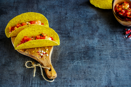 Mexican food. Fresh shrimp tacos with homemade salsa on wooden board over dark slate background. Selective focus, copy space.
