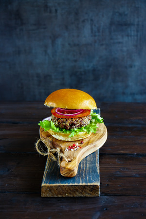 Close up of veggie burger with quinoa patty, lettuce and tomatoes, served on wooden board over dark rustic background, selective focus. Clean eating, detox, vegetarian food concept Stock Photo