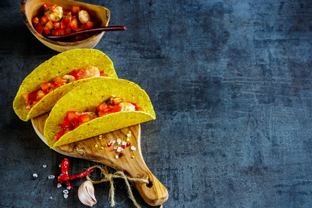 Two shrimp tacos with homemade salsa on wooden board over dark slate background. Selective focus, copy space. Mexican cuisine concept Stock Photo