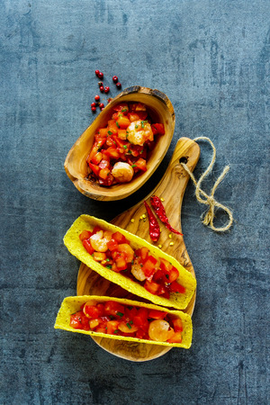 Mexican shrimp tacos with homemade salsa on wooden board over dark slate background. Top view. Mexican cuisine concept