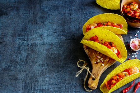Close up of shrimp tacos with homemade salsa on wooden board over dark slate background. Selective focus, copy space. Mexican cuisine concept Stock Photo