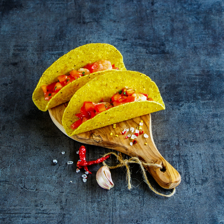 Mexican food on wooden board. Shrimp tacos with homemade salsa over dark slate background. Selective focus, square image.