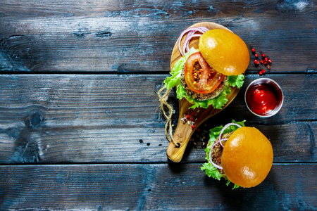 Veggie burgers with quinoa patty, lettuce and tomato sauce, served on rustic wooden board over dark wooden background, top view. Clean eating, detox, vegetarian food concept