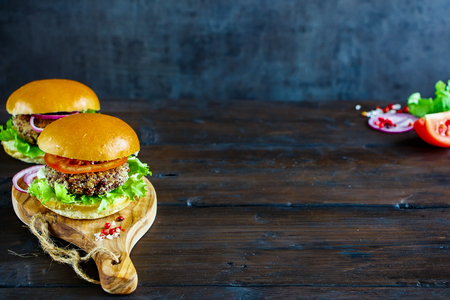 Freshly made veggie burger with quinoa patty, lettuce and tomatoes, served on wooden board over dark rustic background, selective focus. Clean eating, detox, vegetarian food concept Stock Photo