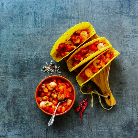 Top view of shrimp tacos with homemade salsa on wooden board over dark slate background. Square image. Mexican cuisine concept
