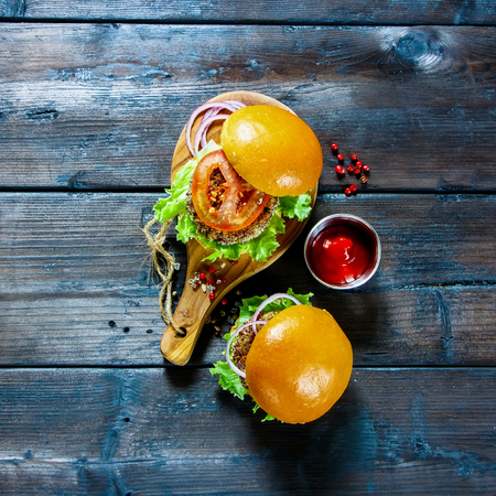 Delicious veggie burgers with quinoa patty, lettuce and tomato sauce, served on rustic wooden board over dark wooden background. Square image. Clean eating, detox, vegetarian food concept