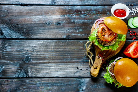 Fresh veggie burgers with quinoa patty, lettuce and tomato sauce, served on little wooden board over dark wooden background, top view. Clean eating, detox, vegetarian food concept Stok Fotoğraf - 82449967