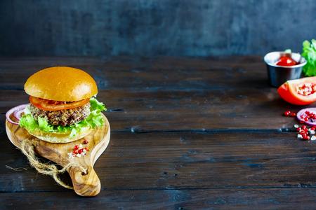 キノアのパテ、レタス、トマトと健康野菜のハンバーガーは、暗い素朴な背景、選択と集中を木の板に提供しています。きれいに食べて、デトック 写真素材