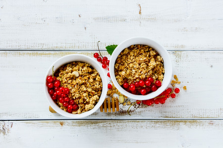 White ceramic bowls of homemade granola with fresh red currants and honey for healthy breakfast over rustic wooden background. Top view