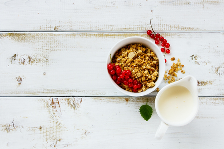 Breakfast on wooden kitchen table. Healthy oat granola in bowl, milk and fresh red currants over white background. Top view, copy space.