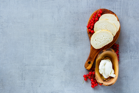 Ingredients for making canape or crostini with baguette, cheese and fresh red currants on wooden board over slate background. Delicious appetizer, ideal as an aperitif. Top view, copy space