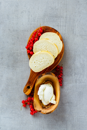Fresh ingredients for making canape or crostini with baguette, cheese and fresh red currants on wooden board over slate background. Delicious appetizer, ideal as an aperitif. Top view, vertical