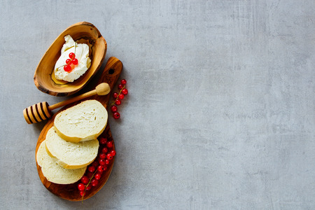 Close up of ingredients for making canape or crostini with baguette, cheese and fresh red currants on wooden board over slate background. Delicious appetizer, ideal as an aperitif. Top view, copy space