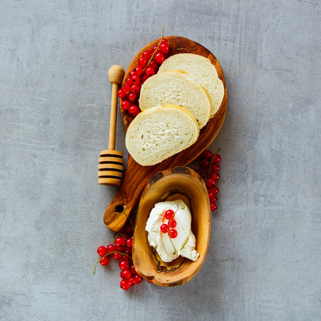 Top view of ingredients for making canape or crostini with baguette, cheese and fresh red currants on wooden board over slate background. Delicious appetizer, ideal as an aperitif. Square crop