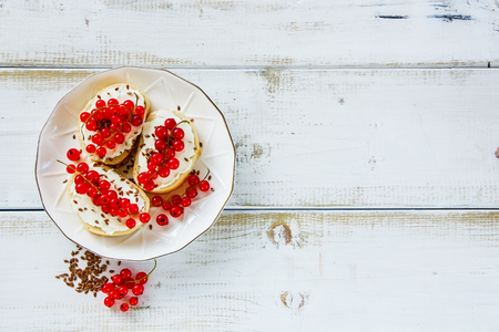 Berry crostinis sandwiches with baguette, cheese, seeds and fresh red currants on plate over white wooden background. Delicious appetizer, ideal as an aperitif. Top view, copy space