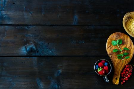 Verse ingrediënten voor het maken van bessenjam met verscheidenheid van bessen, bruine suiker en munt op rustieke achtergrond, hoogste mening, exemplaarruimte. Stockfoto - 84786357