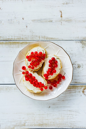 Sweet crostinis sandwiches with baguette, cheese and fresh red currants on plate over white wooden background. Delicious appetizer, ideal as an aperitif. Top view, vertical