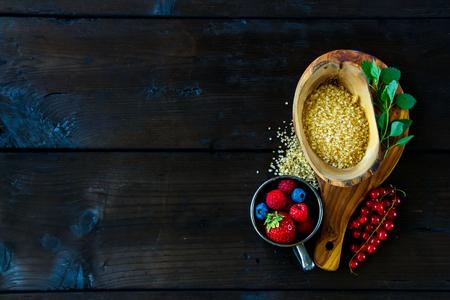 Hoogste mening van ingrediënten voor het maken van bessenjam met verscheidenheid van bessen, bruine suiker en munt op rustieke achtergrond, exemplaarruimte.