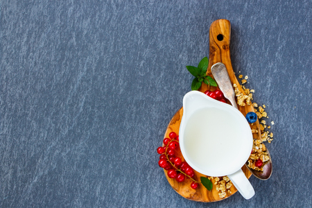 Close up of breakfast ingredients. Jug of milk, homemade muesli and summer berry on wooden board over vintage slate table top view in flat lay style. Healthy breakfast and diet food.