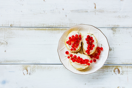 Crostinis sandwiches with baguette, cheese and fresh red currants on plate over white wooden background. Delicious appetizer, ideal as an aperitif. Top view, copy space Фото со стока