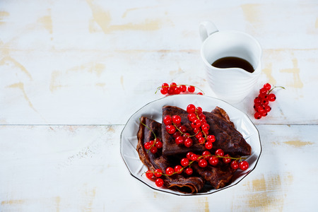 Delicious chocolate crepes with fresh red currants and maple syrop on plate. Light white wooden background. Selective focus. Copy space. Stock Photo