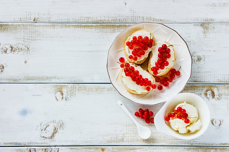 Homemade crostinis sandwiches with baguette, cheese and fresh red currants on plate over white wooden background. Delicious appetizer, ideal as an aperitif. Top view, copy space