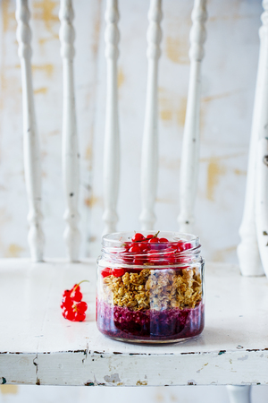 Jar of granola and fresh red currant layered parfait for breakfast on old wooden board, white rustic wall at background, copy space, selective focus. Clean eating, detox food concept, vertical