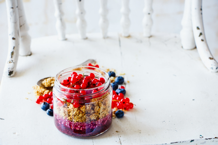 Maison jar of muesli and fresh berry layered parfait for breakfast on old wooden board, white rustic wall at background, copy space, selective focus. Clean eating, detox food concept