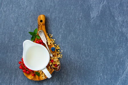 Healthy breakfast ingredients. Jug of milk, homemade muesli and summer berry on wooden board over vintage slate table top view in flat lay style. Healthy breakfast and diet food. Фото со стока