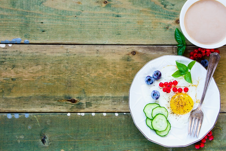 Plate of fried egg with vegetables, berries and herbs, cup of coffee for colorful breakfast on simple wooden background. Top view. Color year. Healthy breakfast concept with copy space.