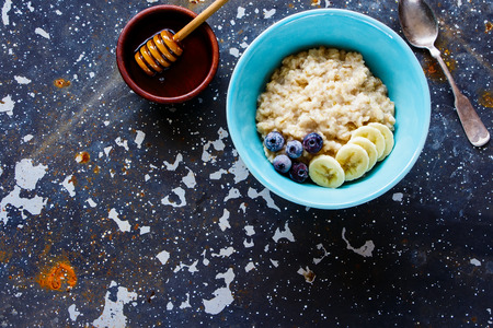 Honey and homemade oatmeal porridge with organic frozen blueberries and banana in bowl on grunge iron table, hot and healthy food for Breakfast, top view, flat lay