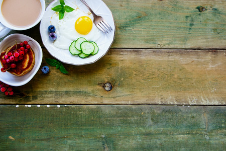 Fried egg with vegetables and herbs, homemade pancakes, coffee and summer berries for breakfast on simple wooden background. Top view. Color year. Healthy breakfast concept with copy space.