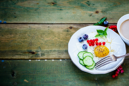 Colorful breakfast of fried egg with vegetables, berries and herbs on plate, cup of coffee over simple wooden background. Selective focus. Color year. Healthy breakfast concept with copy space. Stock Photo
