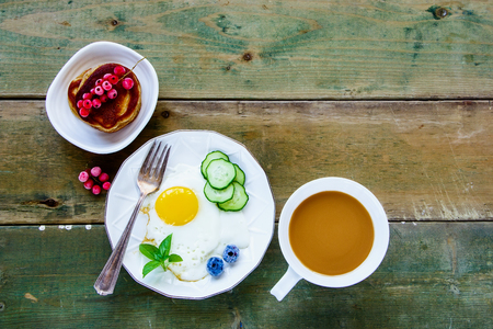 Fresh breakfast with fried egg, cucumber, herbs, homemade pancakes, cup of coffee and organic summer berries on a simple wooden background. Top view. Color year. Healthy breakfast concept with copy space. Stock Photo
