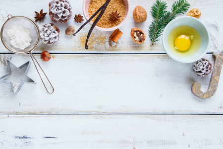 Close up of Christmas baking frame made of sugar, egg, flour, larch branch, pine cones, vanilla sticks, anise star and nuts for christmas cookies. Flat lay, top view Stock Photo