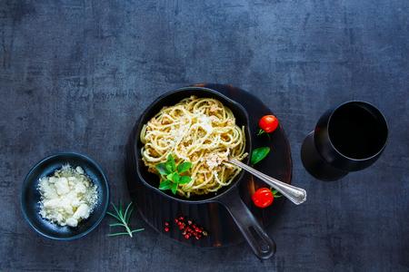 Pasta in padella di ghisa con salsa di granchio cremoso, parmigiano, basilico fresco, pomodori e bicchiere di vino su priorità bassa di pietra dell'annata. Vista dall'alto. Copia spazio Archivio Fotografico - 87150624