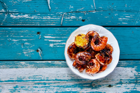 Grilled Prawns Shrimps on plate with lemon on turquoise vintage table from above. Seafood concept. Flat lay
