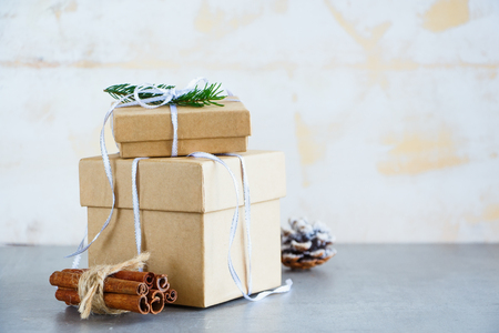 Holiday gift or present box wrapped in kraft paper, Fir Branches and Festive Decoration on Stone Background, Christmas Greeting Card, Selective focus