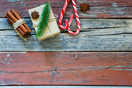 Rustic Holiday wooden background with Christmas Box, Candy Canes, Cinnamon Sticks. Flat Lay Holiday Greeting Card Stock Photo