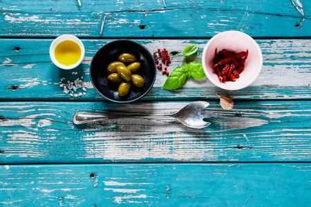 Plat leggen van kommen met ingrediënten voor het gezonde koken op turkooise rustieke achtergrond van hierboven, exemplaarruimte. Dieet, koken, schoon eten of vegetarisch eten.