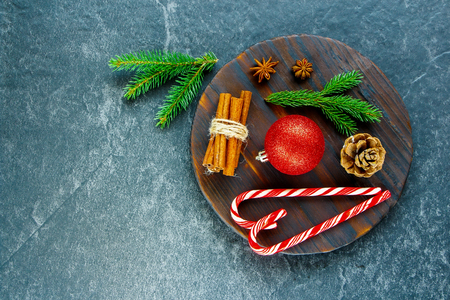 wrappers: Christmas or New Year candy canes, winter spices and festive decorations over wooden board. Winter, holiday concept. Flat lay. Top view Stock Photo