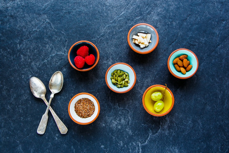 Various Healthy breakfast ingredients with superfood: linseeds, green grapes, nuts, fresh raspberries, coconut chips and pumpkin seeds on dark vintage background, top view, flat lay